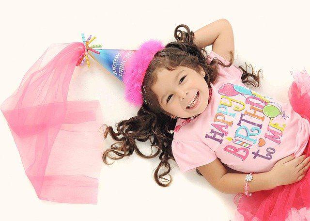 niña con sombrero de colores, cellebrando cumpleaños