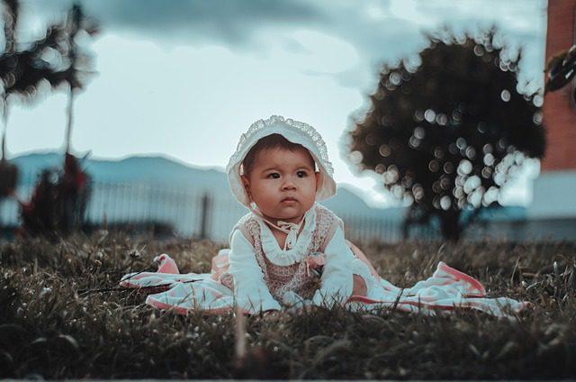 niña en el suelo celebrando bautizo, gorro, niña pequeña